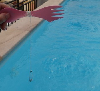 A fishing rod made out of a spork, safety pin and dental floss.